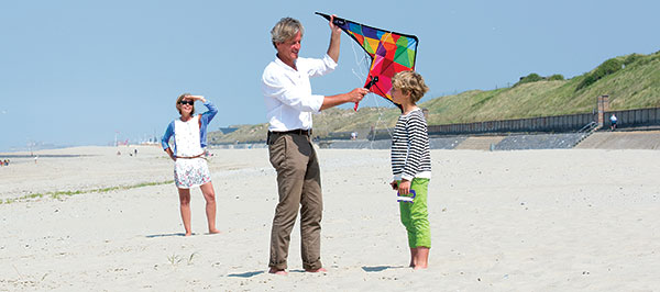 grandparents-and-boy-playing-kite-on-beach